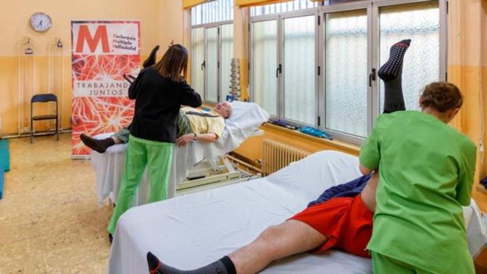 Dos fisioterapéutas de la Asociación Esclerosis Múltiple Valladolid durante una de las sesiones de rehabilitación que desarrollan en sus instalaciones - F. HERAS