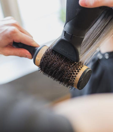 A Stylist doing a a blowout with a round brush and blowdryer. At The Salon by Robert Lupo which is located in Alameda, California.
