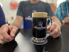 Beer customer holding stout in mug.jpeg