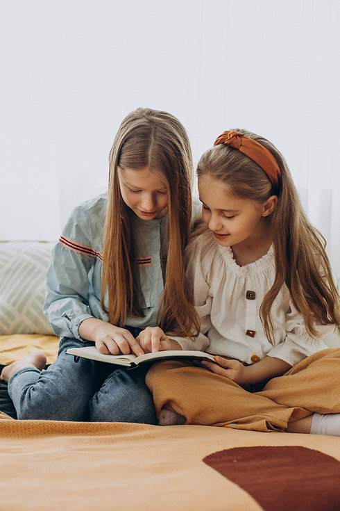 girls-friends-reading-book-together-home