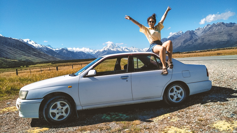 Jess, wearing blue denim shorts and a yellow t shirt, sits on the top of a parked white car with Aoraki/Mount Cook in the background