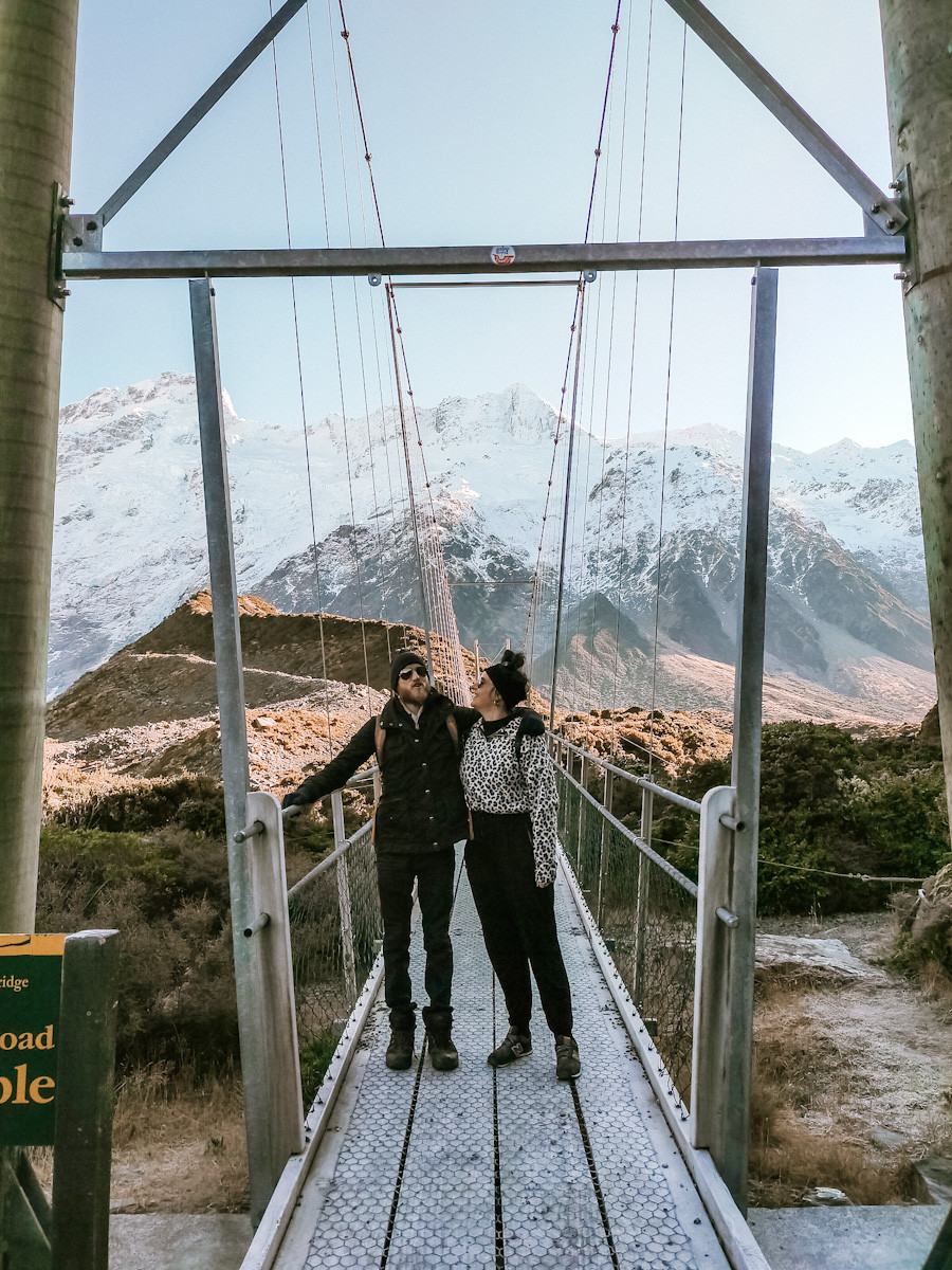 Jess and Jonas stand at the start of a swing bridge with their arms around each other. Jess looks at Jonas. Snow capped mountains in the background