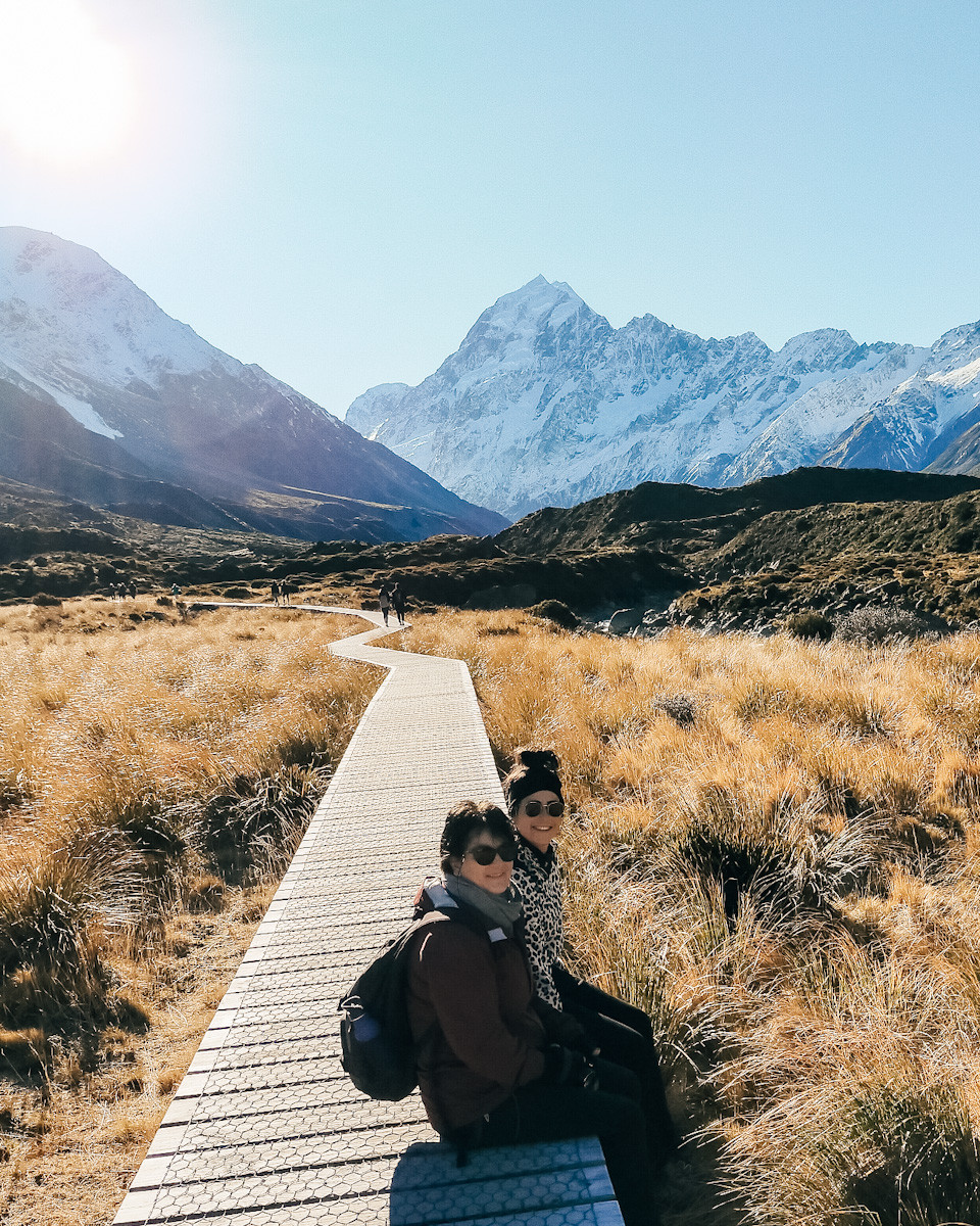 Jess and her mum Marielle sit on the side of a boarded pathway which leads to the snow capped Aoraki/Mt Cook. Yellow shrubs surround the path