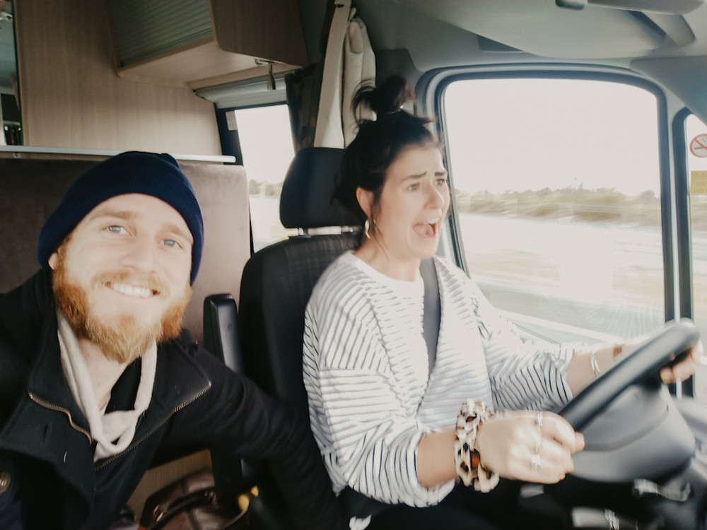 Jonas, wearing a black jacket and a black beanie, smiles while sitting next to Jess. Jess has her black hair in a bun on top of her head and wears a long sleeve black and white stripe top. She is driving the van pulling a stressed out face.