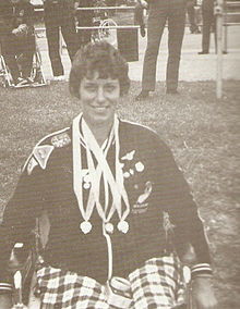 black and white photo of Eve Rimmer in her wheelchair with medals around her neck. She is smiling
