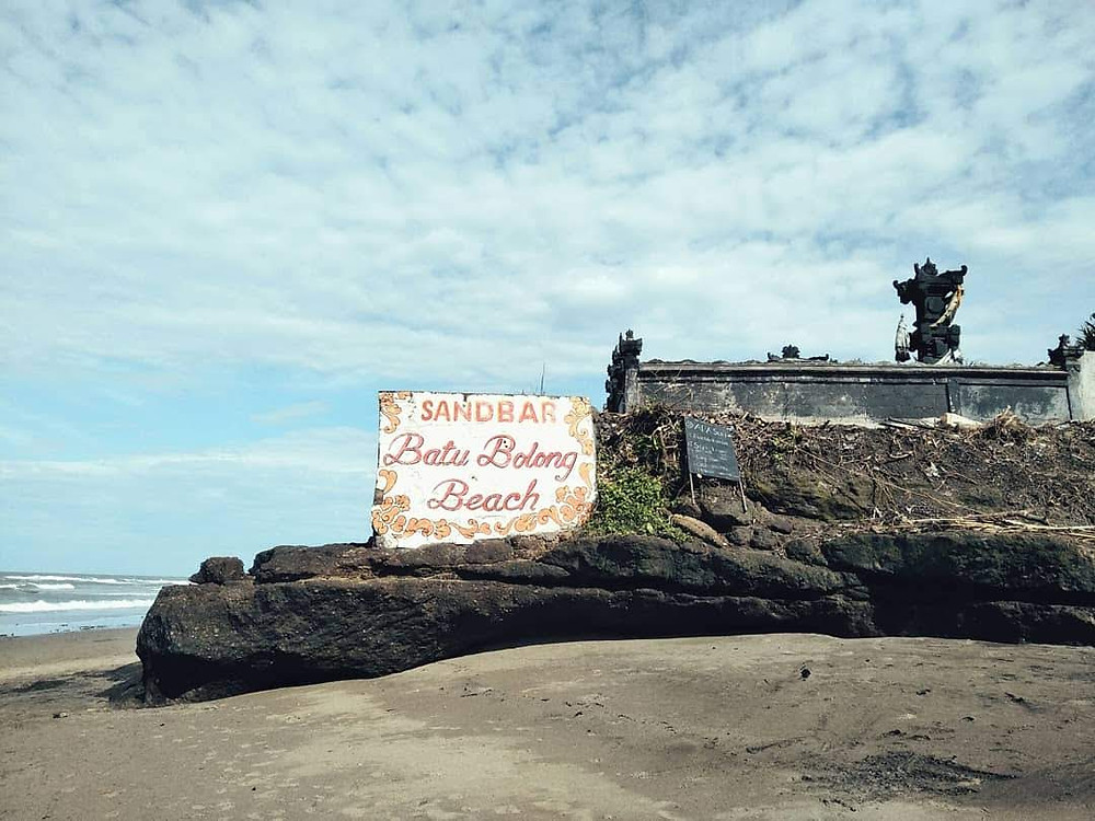 "Blue sky with scattered clouds, black sand beach with a medium sized sign saying ""Sandbar Batu Balong Beach"" sitting on a rock"