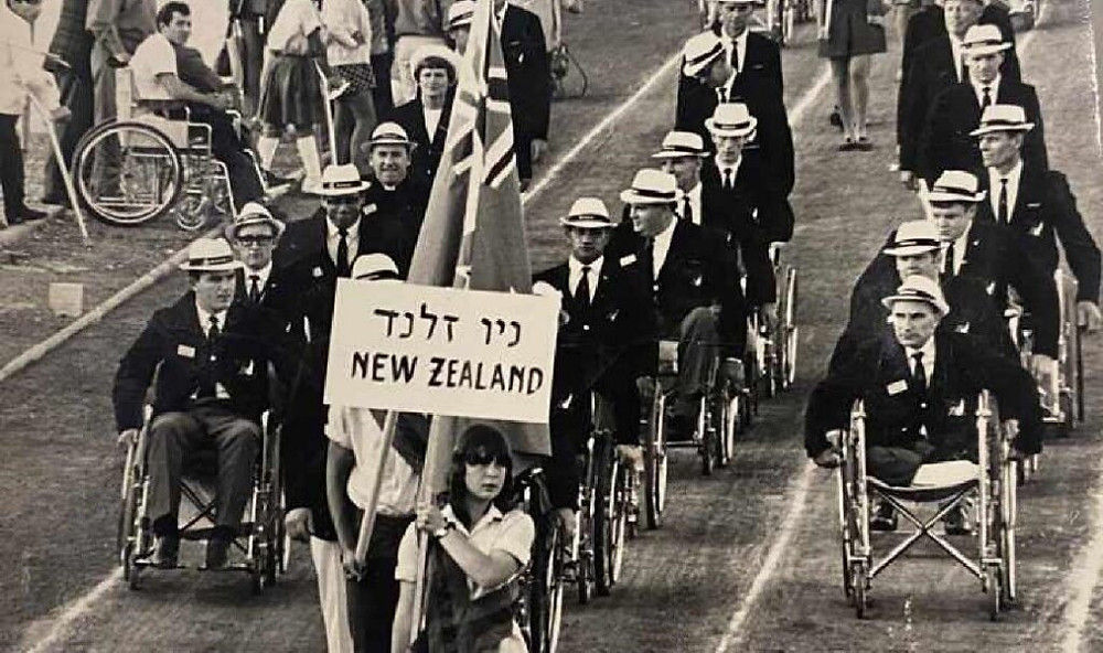 black and white photo of NZ Paralympic Team entering behind a hand held sign that says New Zealand during the opening ceremony