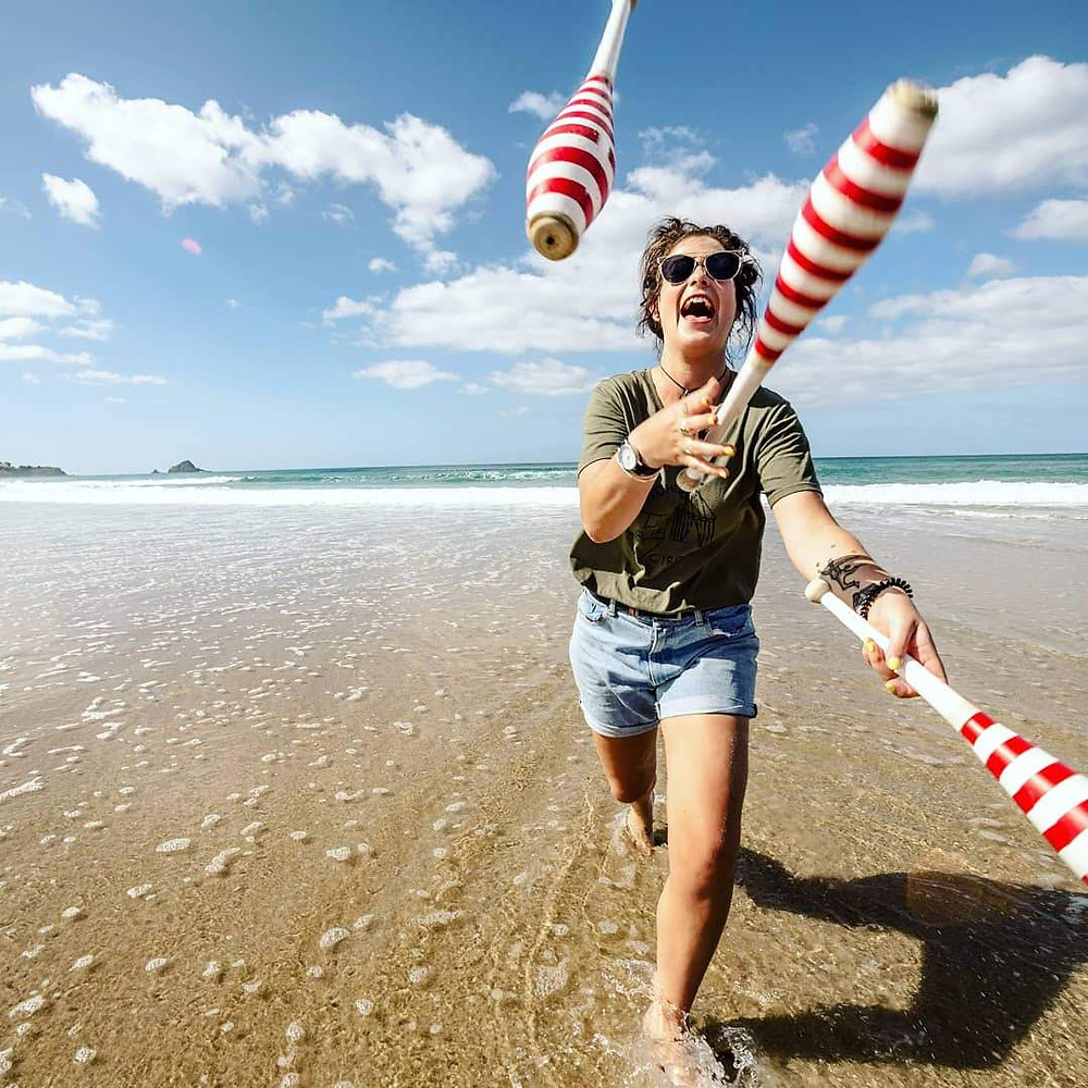Jess, wearing khaki green t shirt, blue denim shorts, aviator sunglasses with her black hair tied up in a bun, running from the ocean to the shore while juggling three red and white strip juggling clubs. Blue sky with fluffy clouds.