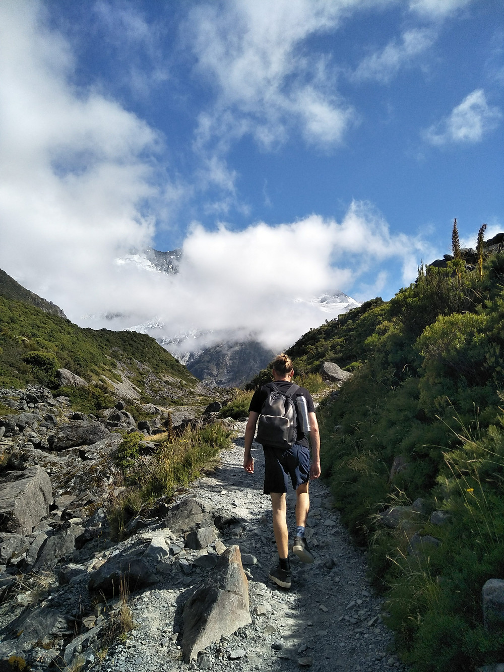 Jonas, wearing a t shirt and shorts with hiking boots and a backpack, walks up a gravel rocky trail towards a snow capped mountain with green shrubs to the side