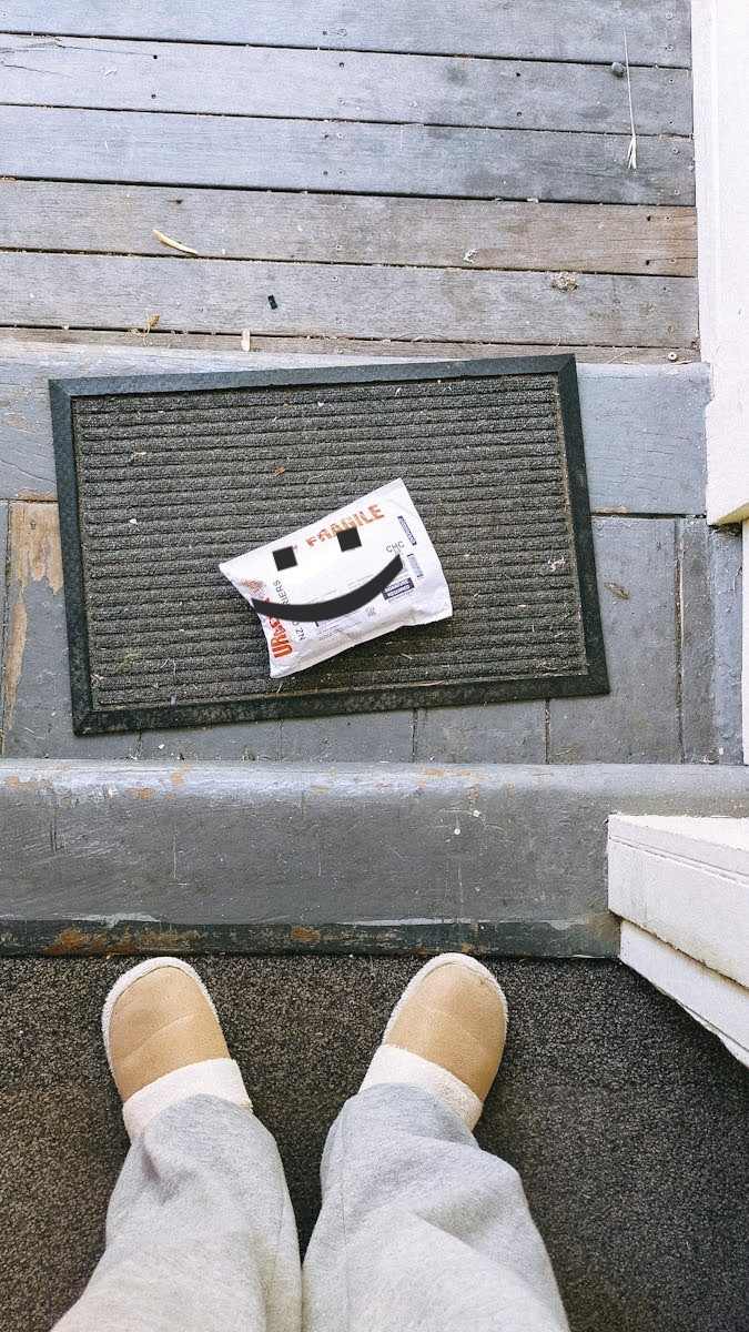 Looking down on a parcel on Jess's doorstep. She is wearing grey trackpants and beige slippers
