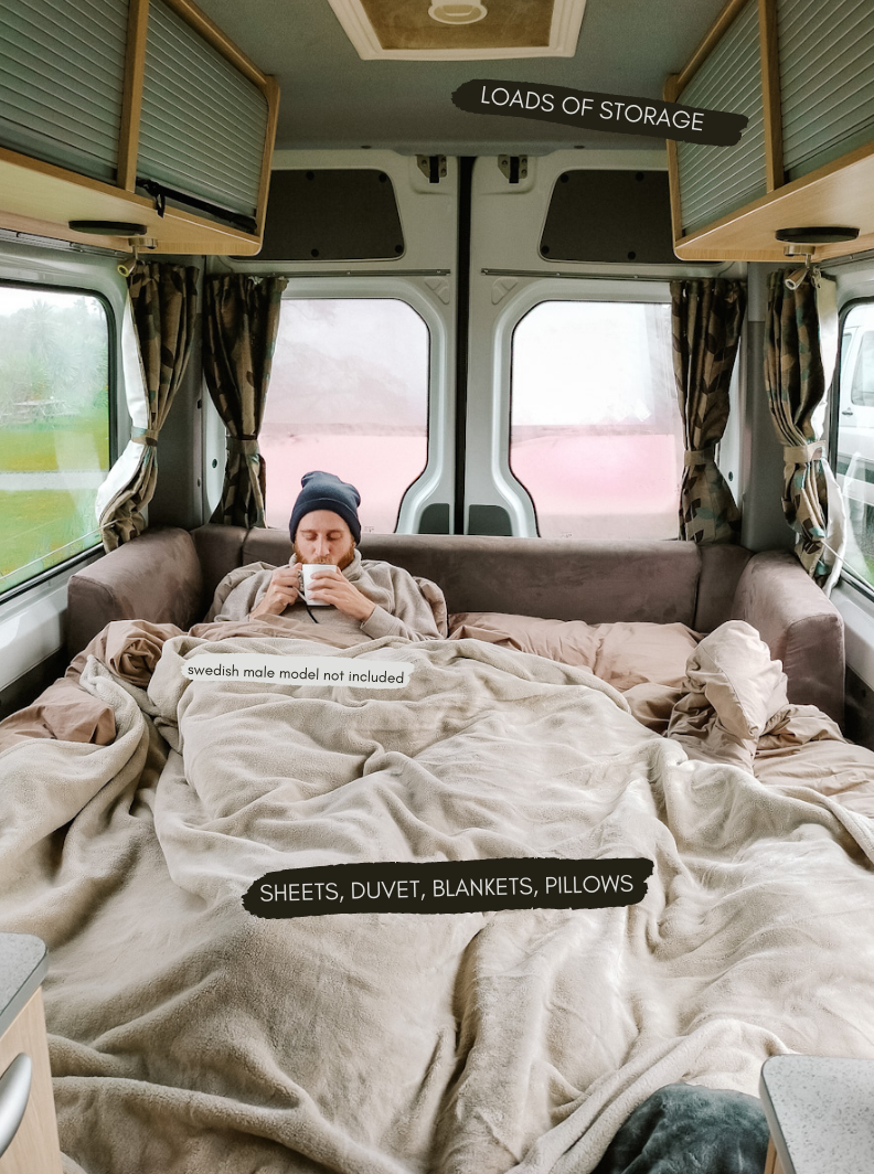 "Jonas is sitting up in the van bed, wearing a black beanie and sipping a cup of coffe. There are description labels labelling everything the van comes with. (written description of this is in the blog text) underneath Jonas it says, ""swedish male model not included'"
