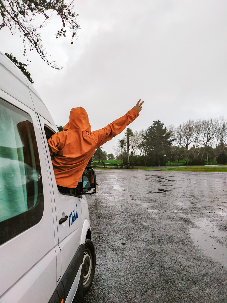 Jess leans out of the driver side window of the van. She wears a bright orange rain jacket and is pulling a peace sign. You can only see her back. It is a dark grey cloudy day and it has been raining. There are puddles on the concrete ground.