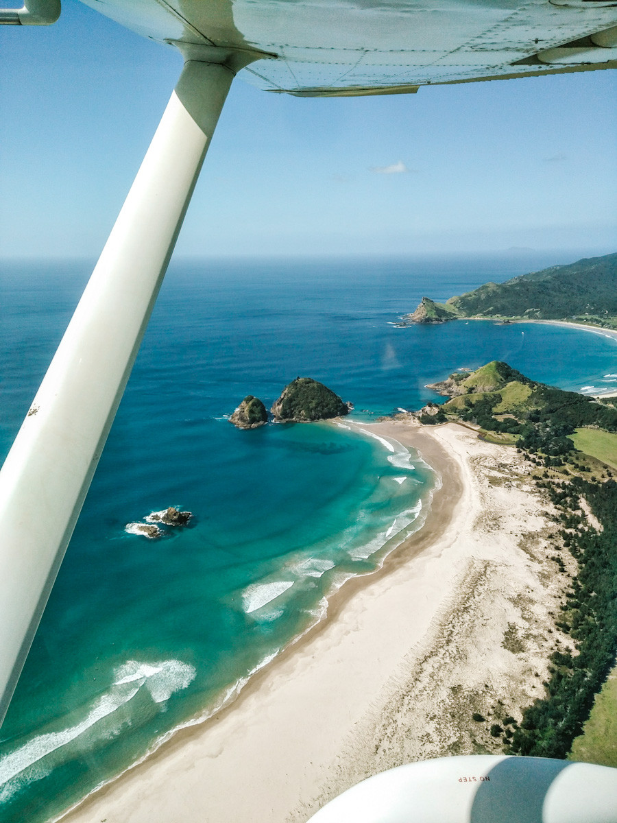 Photo taken out of the window of the airplane. Looking down at a bright blue ocean with a couple of waves, white sandy beach and green hills. You can see a but of the wing at the top of the photo.
