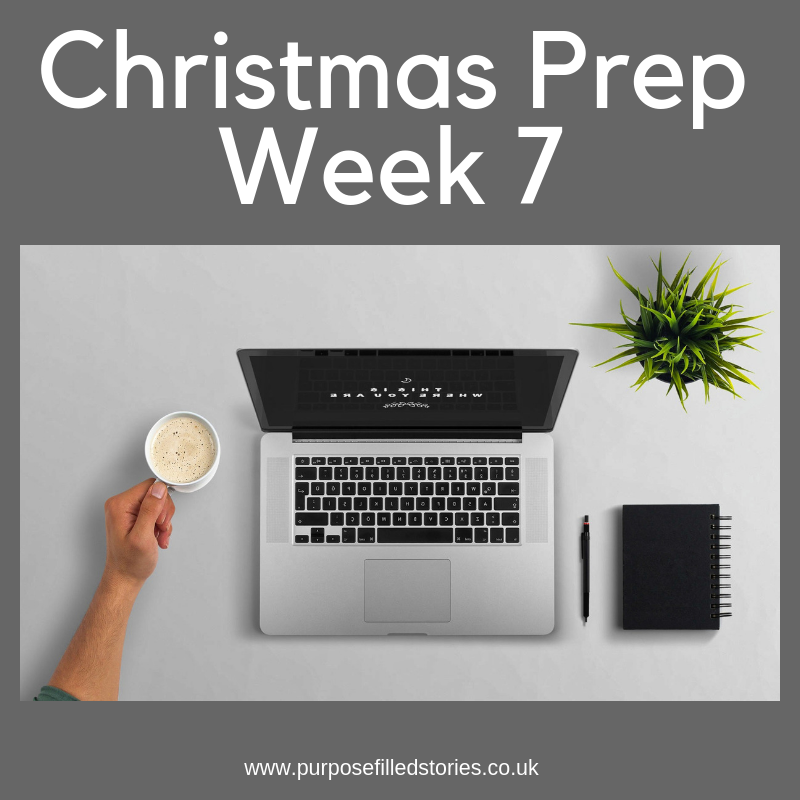 Grey background, white title Christmas Prep Week 7, photograph underneath of laptop, plant, notebook and pen, cup of coffee, under photo white text of grey background website address; www.purposefilledstories.co.uk