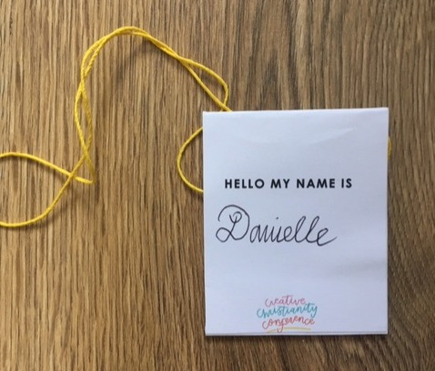 Photograph of name tag, paper folded over which you write on your name and then stick with string threaded through.ck together