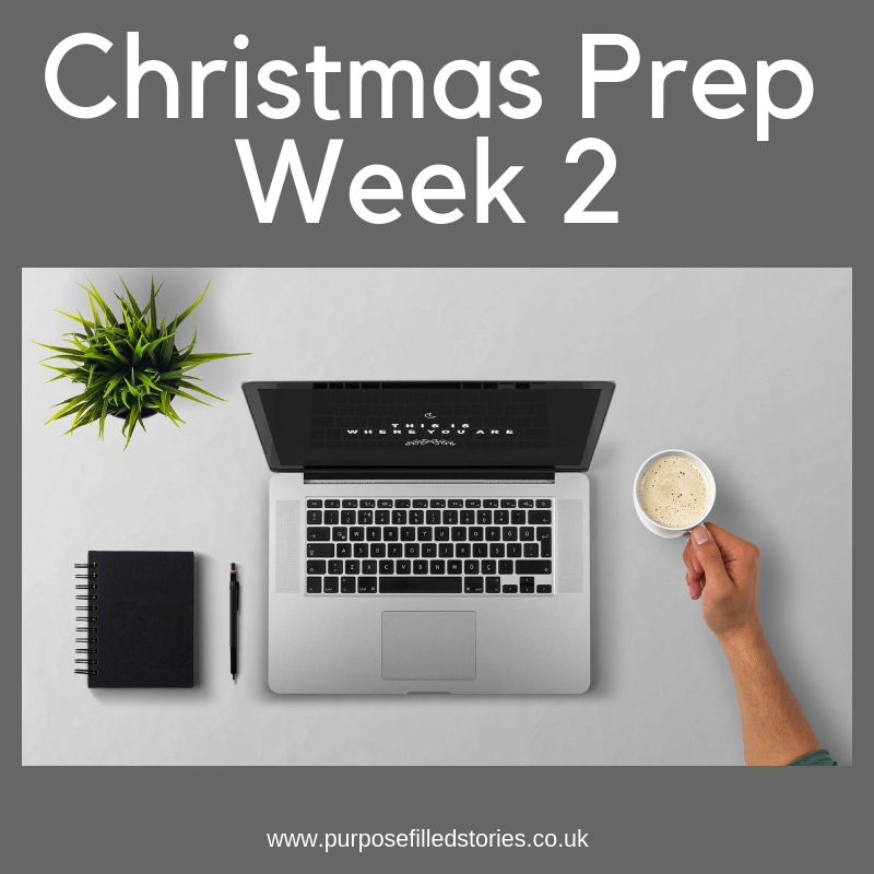 Dark grey background with white writing title - Christmas Prep Week 2 at the top, centre photograph of laptop, notebook pen and coffee mug, bottom white writing against dark grey background of website address - www.purposefilledstories.co.uk