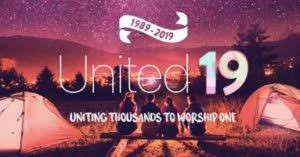 Photograph using red tint of campers overlooking mountain scenery with white writing 1989-2019, united 19, uniting thousands to worship one