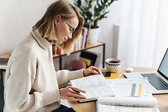 Photo of pleased attractive woman making notes in exercise book and using laptop while sit