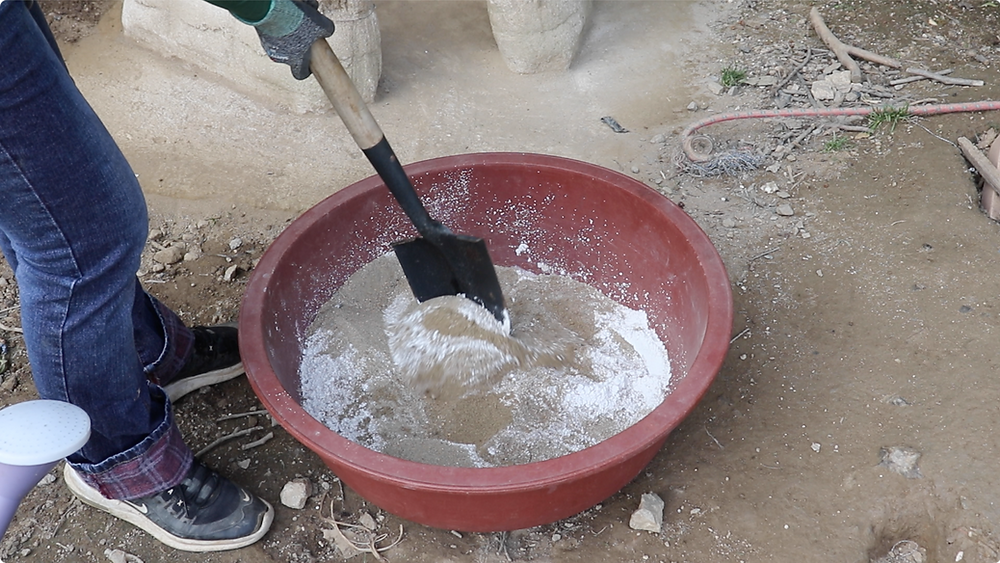 Mixing earthen mixture (soil, sand, and lime)