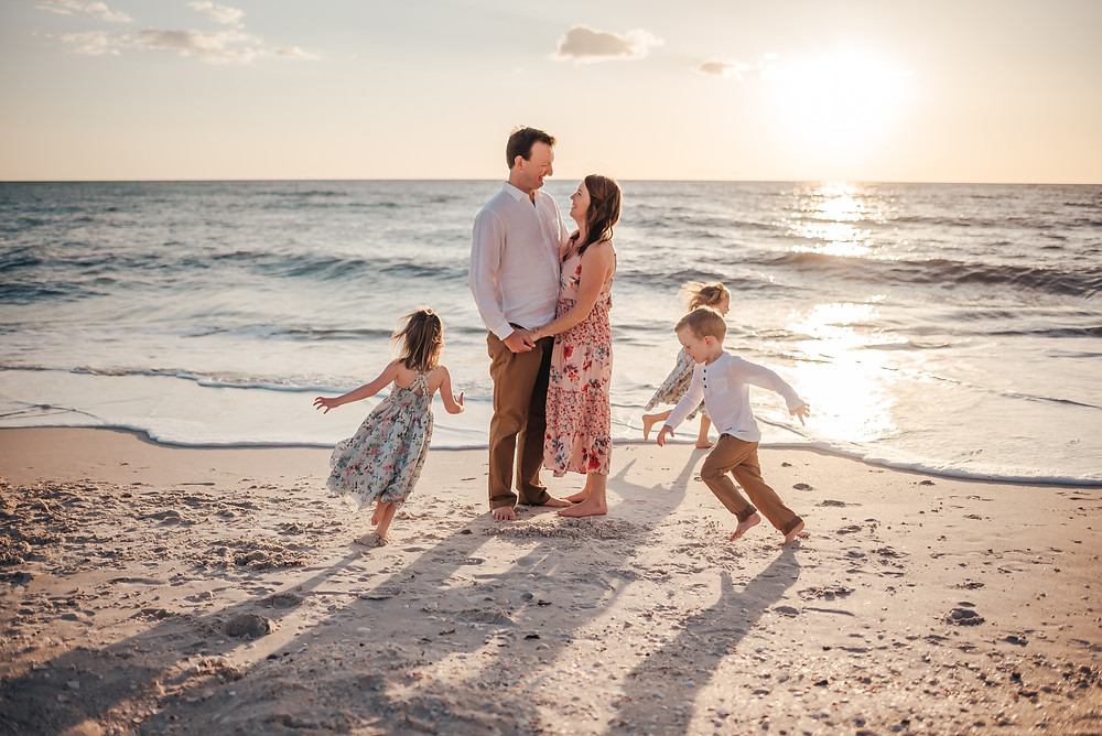 Beach photograph of mom and dad with their children.