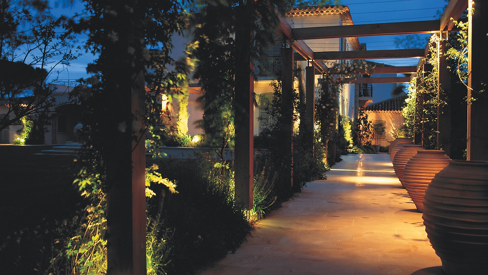 At night, the drama of the pergola is created by small spotlights concealed at a high level, lighting down the posts on the right-hand side.