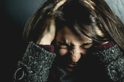 Eine Frau greift sich frustriert in die Haare.