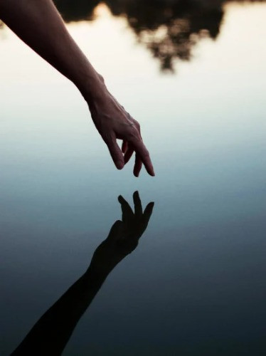 eine Hand spiegelt sich im Wasser und erzeugt das Bild einer sanften Berührung