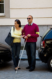 Woman helping blind man