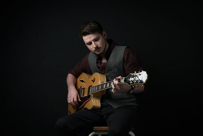 Tom is holding and looking at an electro-acoustic guitar