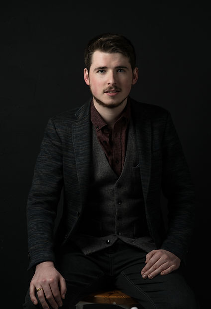 Photograph of Tom in a 3-piece suit, sat looking directly at camera