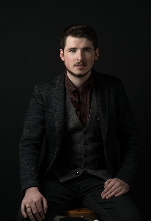 Musician  sat in a suit with a waistcoat