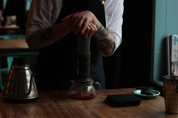 man-with-blue-apron-brewing-coffee-using