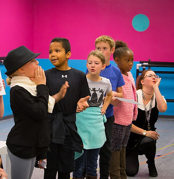 Five young people performing and an instructor on her knees cheering them on in a pink room.