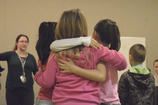 Three young people hugging, shot from behind while a female teacher teaches.
