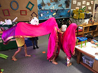 Three young people in a classroom playing pretend under a pink piece of fabric.