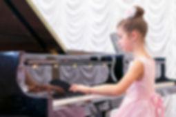 girl in a beautiful pink dress playing o