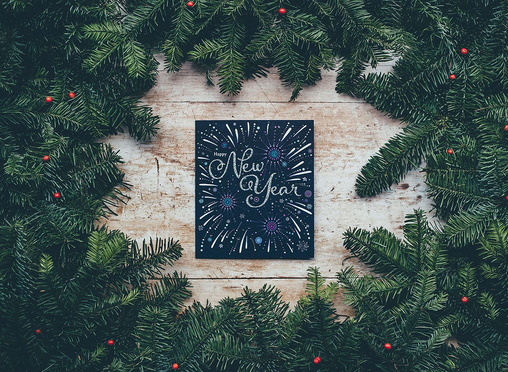 Happy New Year written on a blackboard surrounded by Christmas greenery