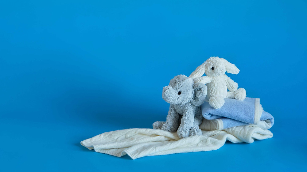 Soft toys and cloths for baby against blue background