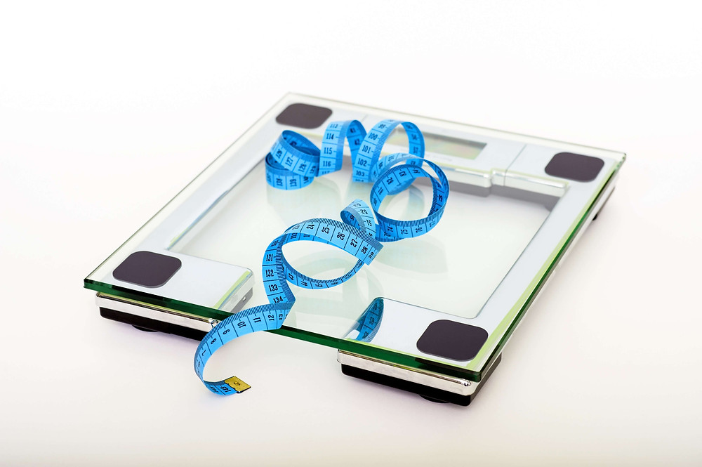 Glass bathroom scales and blue measuring tape