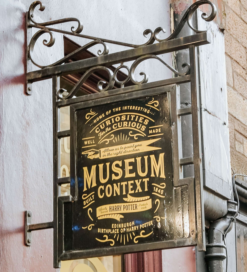 A black museum sign with gold lettering