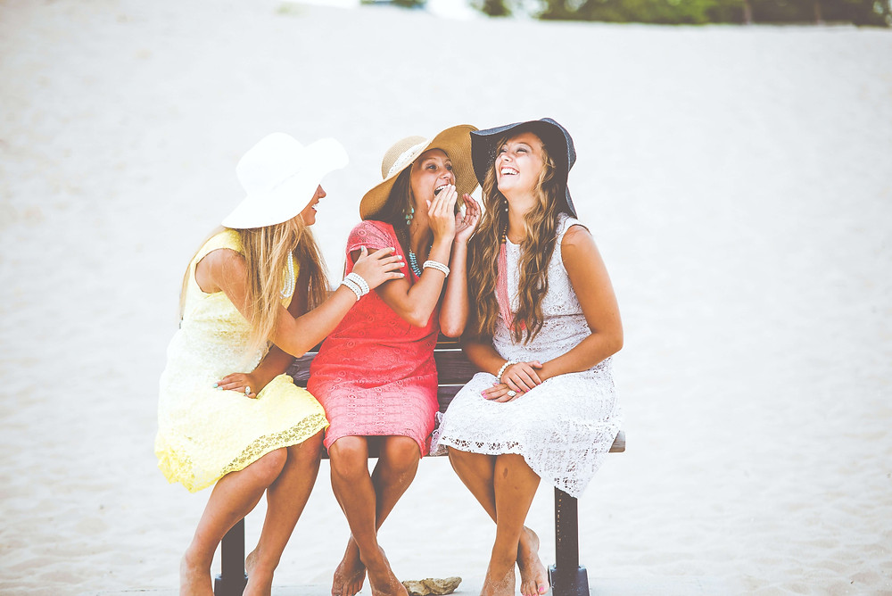 Three female friends talking together and laughing