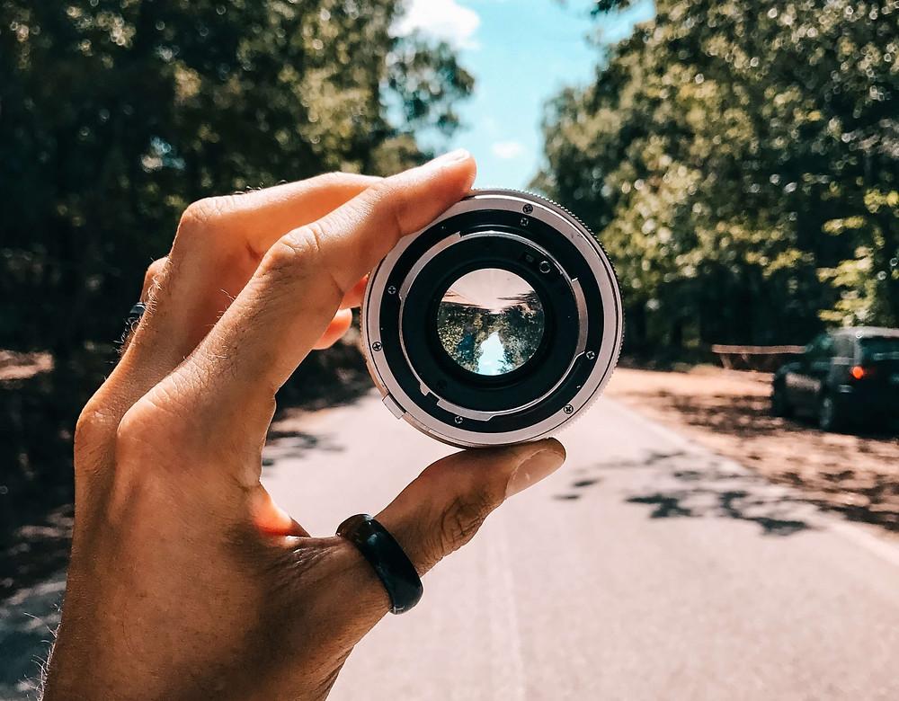 Hand holding a camera lens
