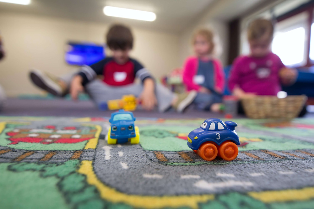 Two blue cars on a mat with a road and three children in the background