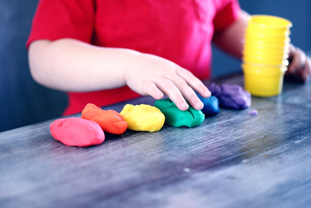 Child playing with play doh in rainbow colours