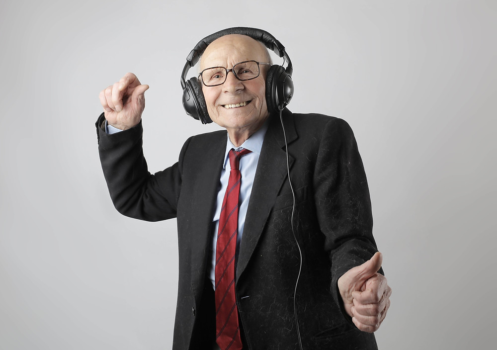 Smiling old man listening to music on headphones