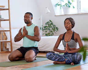Calm relaxed couple meditating at home d