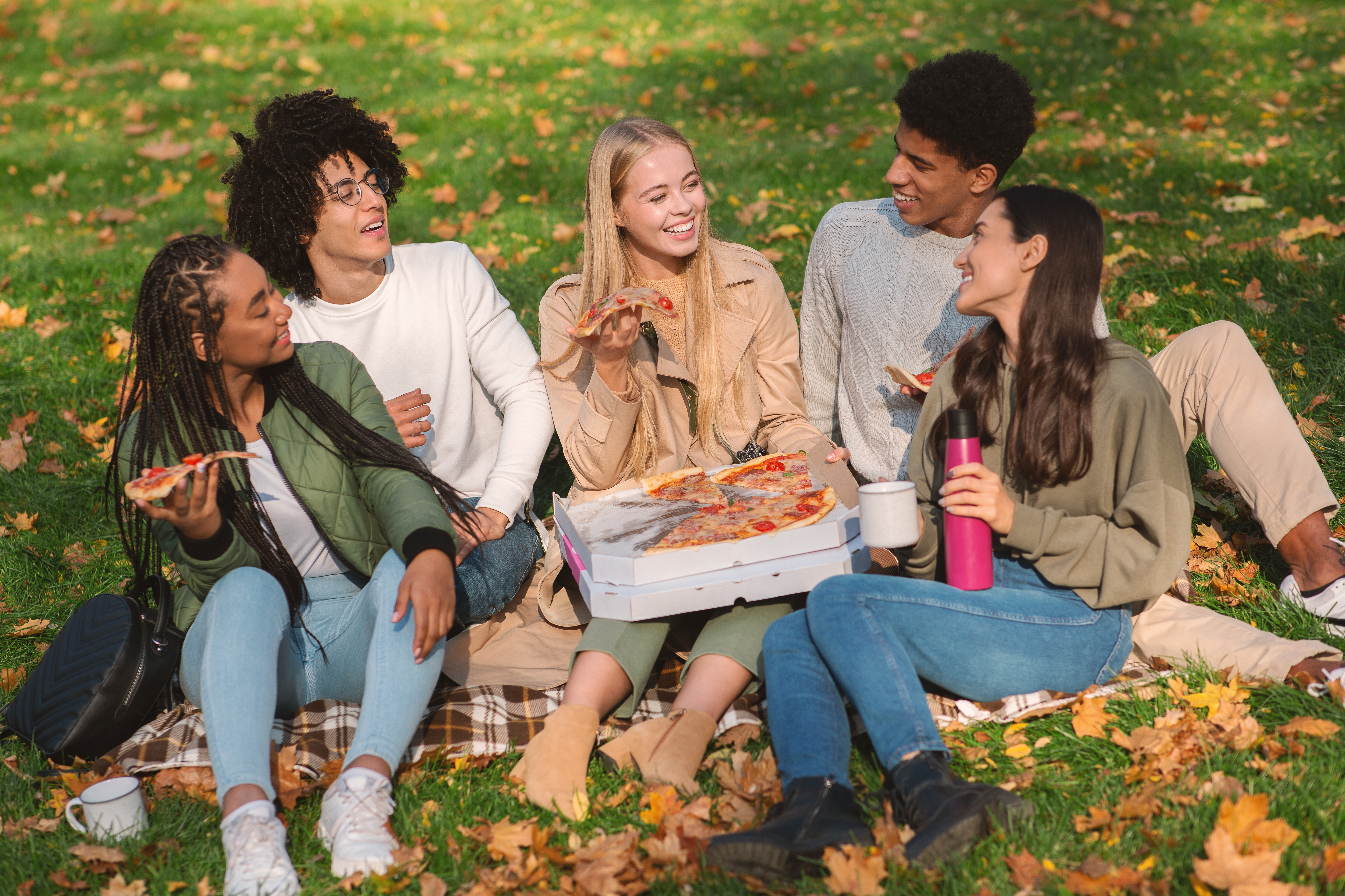 cheerful-friends-eating-pizza-at-public-