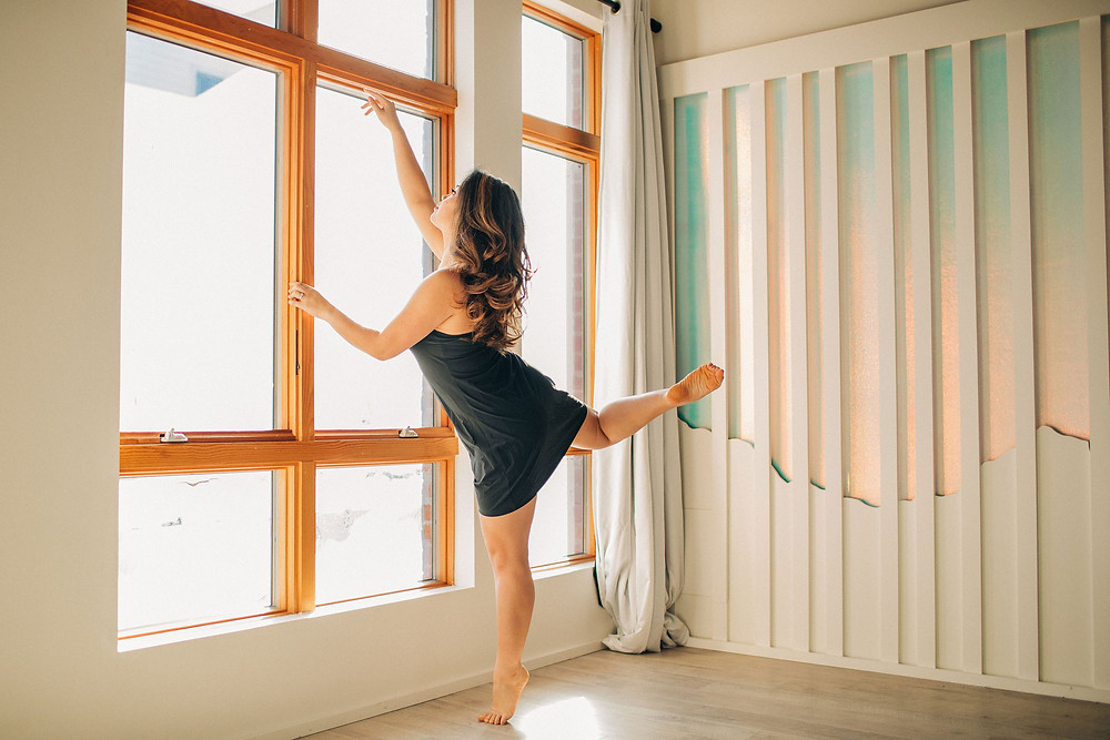 Lauren DeVera dancing in front of a window