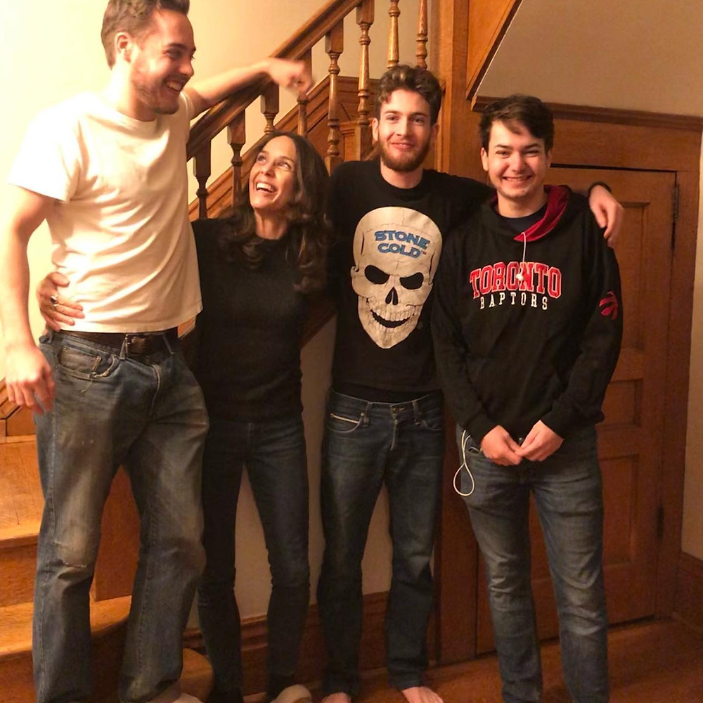 Cathy with her three tall sons, the oldest standing on the stairs to boost his height