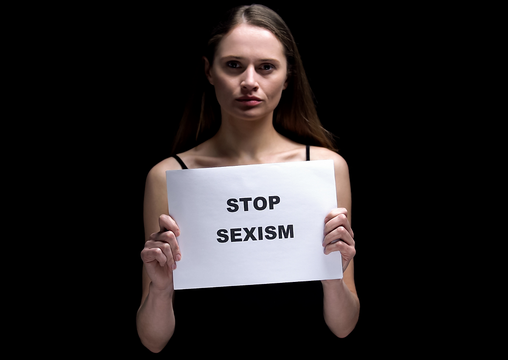 """Woman holding sign that says """"Stop Sexism"""""""